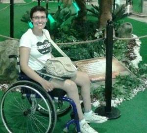 Daniela a bordo de sua cadeira em um cenário todo verde