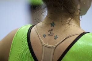 """Detalhe de uma tatuagem na altura da nuca de Laís. A letra """"L"""" rodeada por três estrelas"""