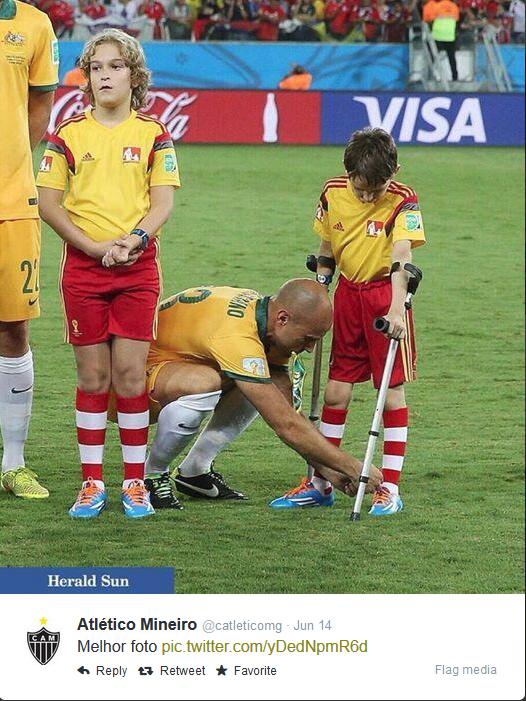 Reprodução de imagem postada no Twitter no Atlético Mineiro, que mostra o momento em que Mark se abaixa para amarrar o cadarço da chuteira de Alan Crédito: Reproducao/@catleticomg/heraldsun/George Salpigtidis