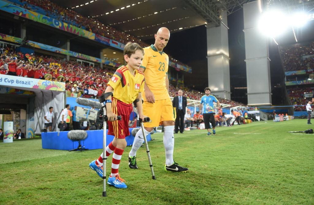 Jogador da Seleção da Austrália observa garoto entrar em campo de muletas