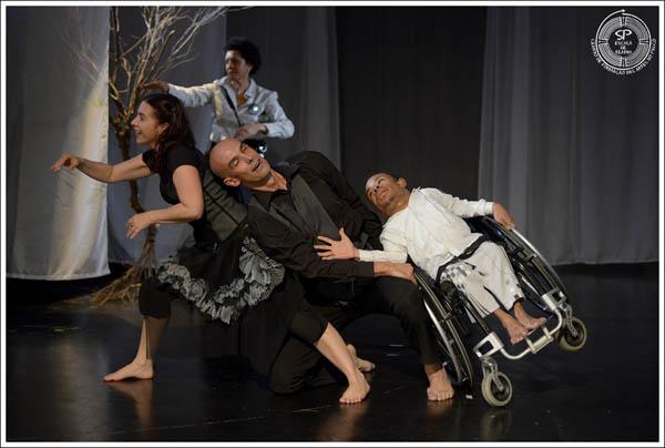 Como se caíssem um sobre o outro, um cadeirante e um bailarino vestindo preto. Os dois sendo amparados por uma bailarina  Crédito: Andre Stefano