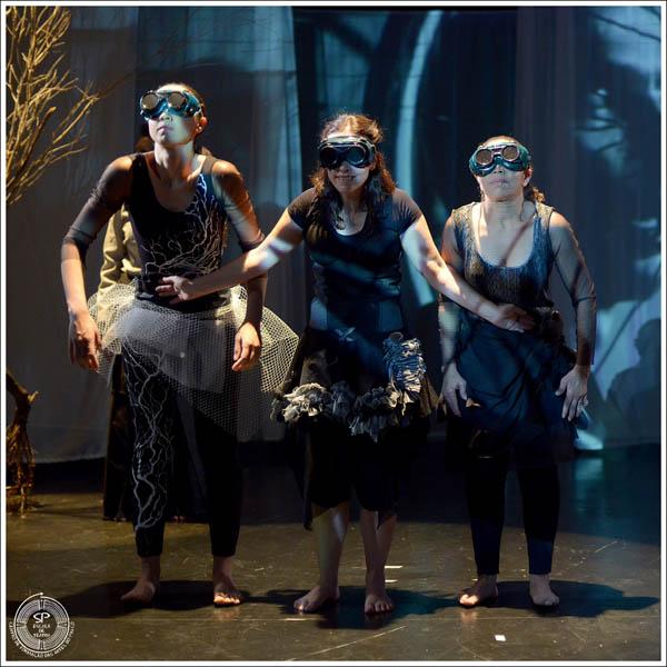 Três bailarinas com os olhos vendados por uma espécie de binóculos no centro do palco Crédito: Andre Stefano