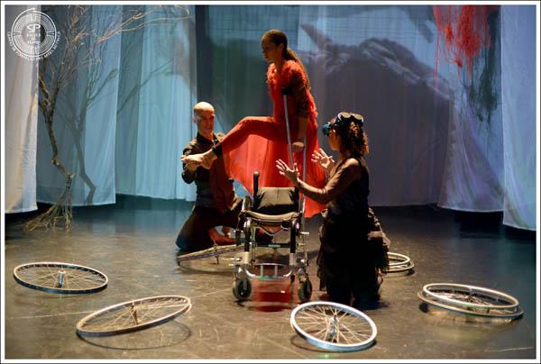Uma bailarina é sustentada acima de uma cadeira de rodas por dois outros bailarinos. Ao redor deles, várias rodas Crédito: Andre Stefano