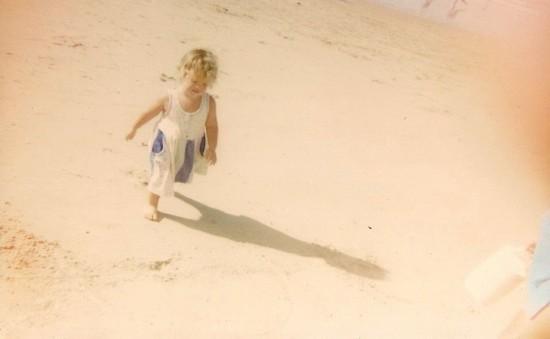 Maria Paula, ainda bem pequena, caminha na areia. Dores apareceram bem cedo