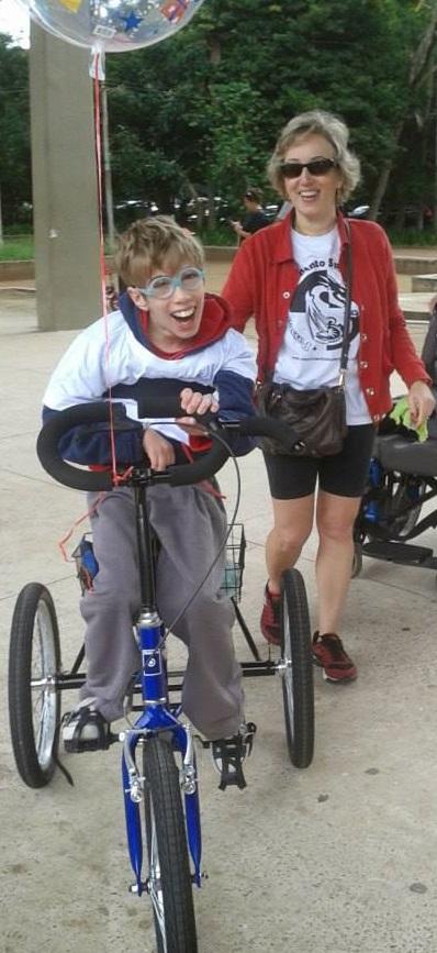 André, todo felicidade, montado em sua nova bicicleta azul. Ao fundo, sua mãe, Lina
