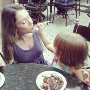 Verônica recebendo comida de uma menininha na boca