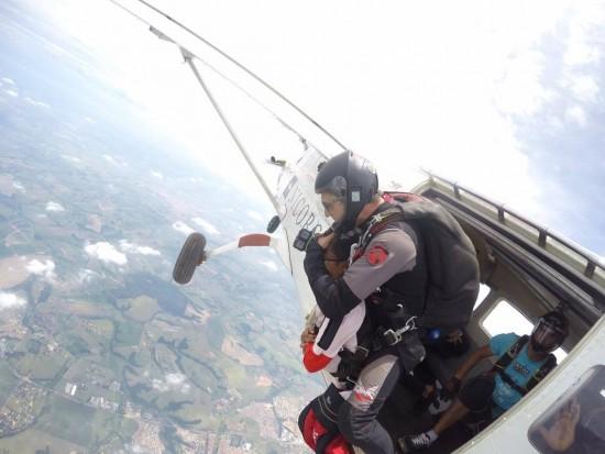 Momento em que Leandro sai do avião, com o instrutor, para o salto